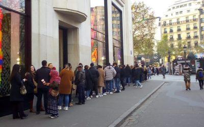 Uma mulher fora do cenário, numa fila em Paris