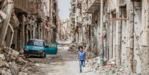 Unicef_Giovanni Diffidenti Crianca corre entre destruicao em Benghazi, na Libia