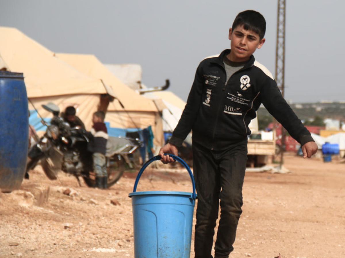 OCHABilal al Hamoud Crianças levam baldes com água em campo de deslocados na Síria
